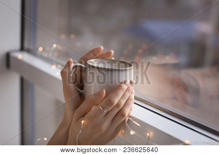 Young Woman With Cup Of Hot Coffee Near Window, Closeup