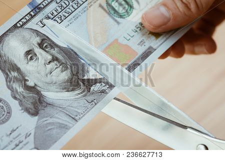 Women Hand Holding Scissors Cutting Us Dollar Banknotes, Cut Budget, Reduce Cost Or Sale At Half Pri
