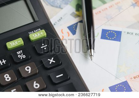 Currency, Economic, Cost Or Expense Concept, Black Pen On Pile Of Euro Banknotes With Calculator.