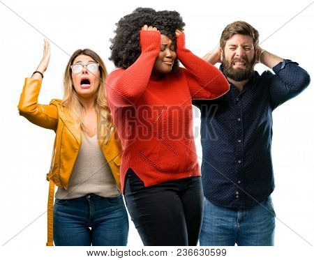 Group of three young men and women terrified and nervous expressing anxiety and panic gesture, overwhelmed
