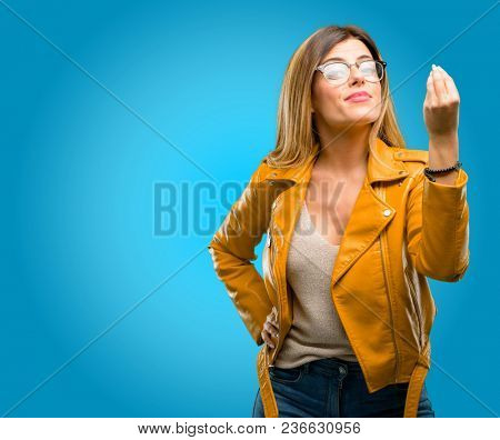Beautiful young woman angry gesturing typical italian gesture with hand, looking to camera, blue background