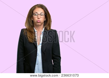 Middle age business woman puffing out cheeks, having fun making funny face