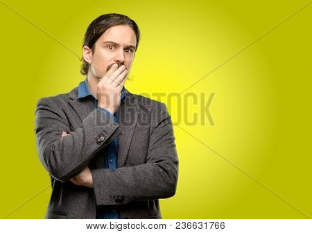 Handsome young man covers mouth in shock, looks shy, expressing silence and mistake concepts, scared