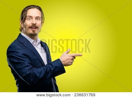 Handsome young man pointing away side with finger