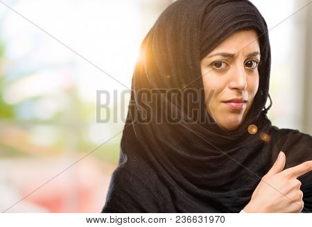 Young arab woman wearing hijab pointing away side with finger