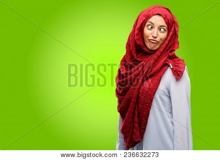 Young arab woman wearing hijab making funny face fooling