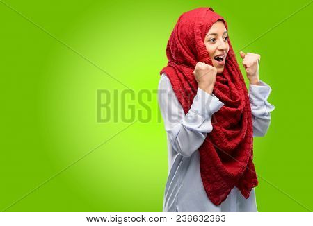 Young arab woman wearing hijab happy and excited expressing winning gesture. Successful and celebrating victory, triumphant
