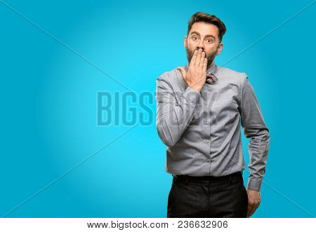 Middle age man, with beard and bow tie covers mouth in shock, looks shy, expressing silence and mistake concepts, scared