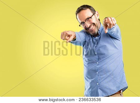 Handsome middle age man pointing to the front with finger