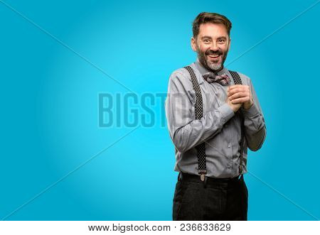 Middle age man, with beard and bow tie confident and happy with a big natural smile in love