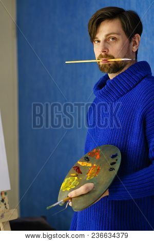 Artist In Blue Sweater Holds Brush In His Mouth. He Holds Palette, Bristles And Palette Knives In Hi