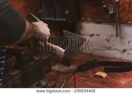 Man Works In Carpentry Workshop. He Straightens Ax Blade On Wooden Handle With Hammer. Men At Work.