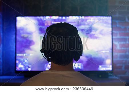 Gamer or streamer in earphones with microphone sits at home in dark room and plays with friends on networks in video games. The young man is angry and grabs his head, as his team lost the game. poster