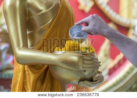 Songkran Festival In Thailand, Hands Man Use The Water Pouring To Golden Buddha