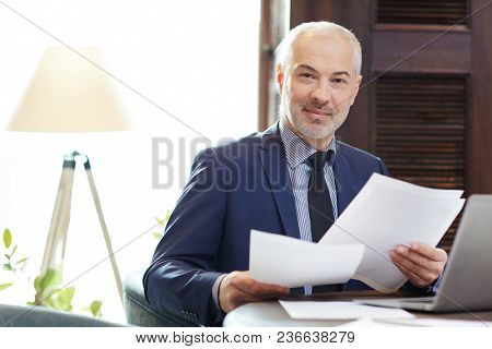 Portrait of confident gray-haired Caucasian man in business attire sitting at table with papers and smiling at camera