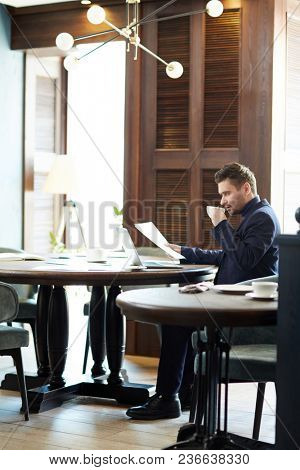 Attractive Caucasian man in business attire sitting at large round table, drinking coffee and looking through documents