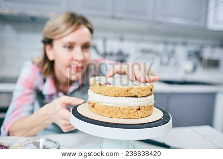 Defocused Caucasian female cook finishing appetizing layer cake with cream in kitchen