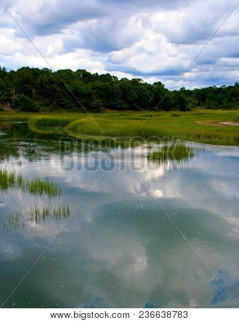Reflections Of Fluffy Clouds On Calm, Still Water On Cape Cod Massachusetts.