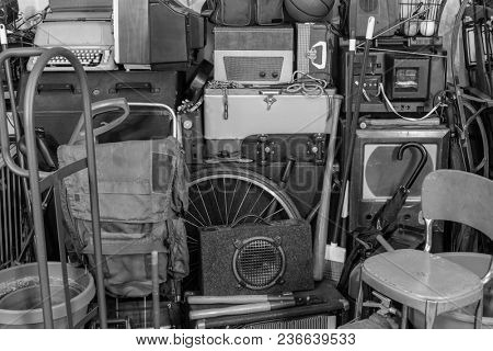 Vintage garage storage area with old tools, gardening, music and sports equipment in black and white.