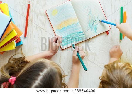 Two  Girls Of Eight And Two Years Draw Colored Pencils, Play On A Floor. Children's Creativity. Home