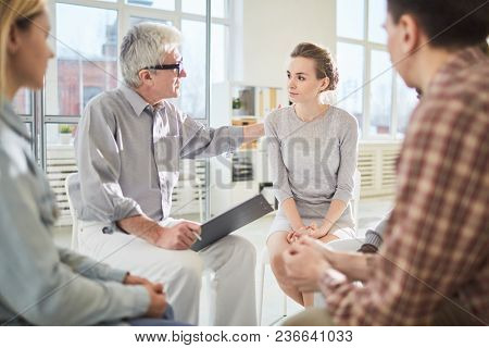Senior man communicating with group during psychotherapy