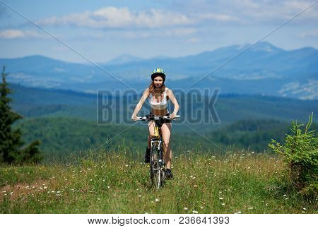 Active Girl Biker Riding On Yellow Mountain Bike On A Grass, Wearing Helmet, On Sunny Day. Mountains