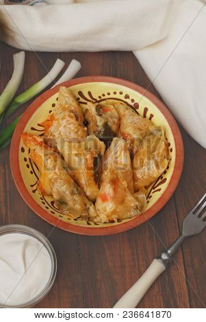 Stuffed Rolled Cabbage Meat In Leaves In A Ceramic Plate With White Napkin, Rustic Wooden Background