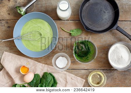 Top View Set Of Raw Ingredients For Cooking Healthy Spinach Pancakes On Wooden Table (dough, Flour,