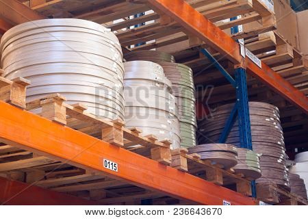 Furniture accessories. Multicolored bobbins of PVC edge and melanin for the manufacture of furniture. Lie pyramid. Selective focus. There is free space for text. poster