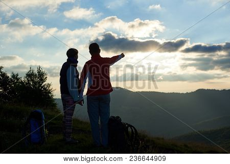 Rear View Two Tourists Are Standing On Top Of The Mountain Holding Hands Near Backpacks Against The