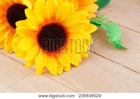 Yellow Fabric Daisies On A Wooden Background.