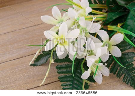 White Artificial Flowers On Wooden Background, Closeup Picture.