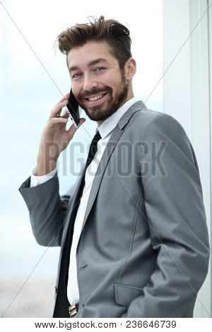 A businessman in a smart suit talking on a mobile phone