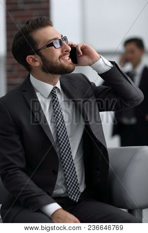Charming businessman talking on phone  in a modern building