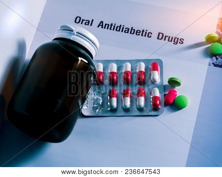 Diabetes Drugs In Packs And And Medicine Bottle With Blank Label Placed On Textbook. Green Tablets A