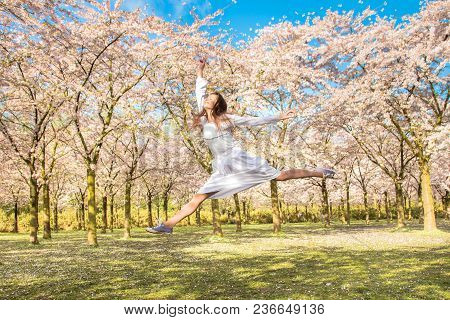 Happy Teenager He Is Laughing And Jumping Up. Teen Girl In Spring Blossoming Garden. Teenager And Bl
