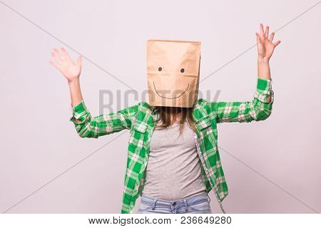 Happy Unknown Woman With A Paper Bag On Her Head On White Background.