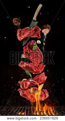 Flying pieces of raw beef steaks from grill grid, isolated on black background. Concept of flying food, very high resolution image