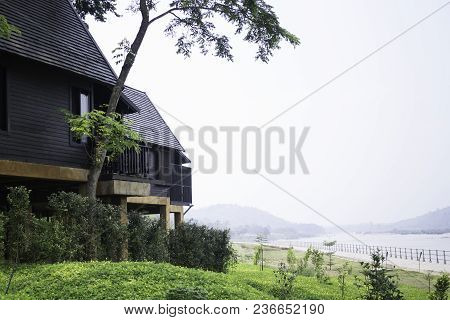 Wooden House With Green Garden Beside The River, Stock Photo
