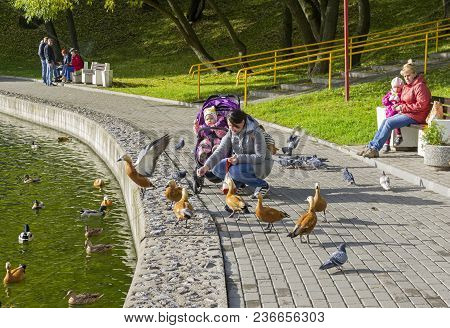 Moscow, Russia, October 10, 2017: A Woman With A Baby Feeds Ducks On The Quay Pond. The South-wester