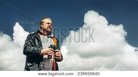 Male Traveler Looking Through Binoculars In The Distance Against The Sky. Low Angle Point Shoot With
