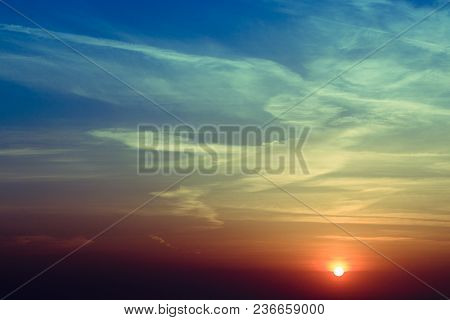 Natural Sunset Sunrise Over Field Or Meadow. Bright Dramatic Sky And Dark Ground. Countryside Landsc