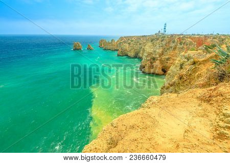 Spectacular Algarve Coast With Ponta Da Piedade Lighthouse In The Distance. Lagos, Algarve In Portug