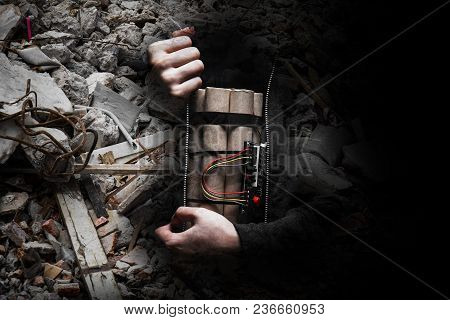 Man In A Black Jacket Strapped With Explosives And Detonator Holds In His Hand