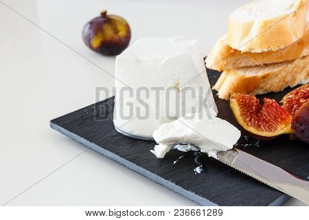 Goat Cheese, Fresh Ripe Fruit Figs And Freshly Baked French Baguette. Light Background.