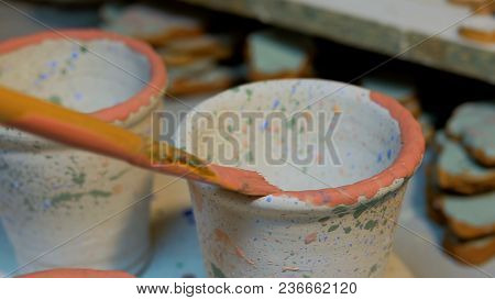 Professional Male Potter Painting Mugs In Pottery Workshop, Studio. Crafting, Artwork And Handmade C