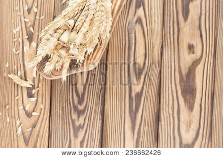 One Bundle Of Wheat And Poppy On Brown Cutting Board And Lot Of Scattered Grain On Old Rustic Wooden