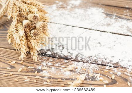One Bundle Of Wheat And Poppy And Strewn Flour On Old Rustic Wooden Planks
