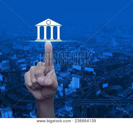 Hand Pressing Bank Icon Over Modern City Tower, Street And Expressway, Business Banking Concept