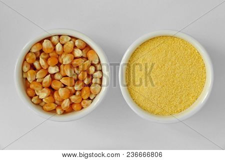 Dry Corn Kernels And Corn Flour In Bowl On White Background